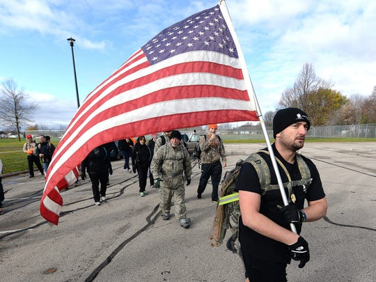 Army veteran Aaron Schmallenberg carries the U.S. flag as a group of Carry the Fallen marchers leave Ft. Howard Park to continue taking part in a national ruck march event around the Green Bay area to reduce veteran suicides November 8, 2014.
