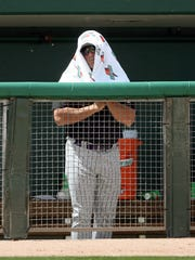 Chip Hale covers his head with a towel for protection
