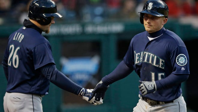 Seattle Mariners' Kyle Seager (15) is congratulated by Adam Lind after Seager hit a solo home run in the sixth inning of a baseball game against the Cleveland Indians, Tuesday, April 19, 2016, in Cleveland.