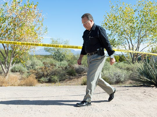 "Doña Ana County Sheriff's Office Investigator Robert ""Bo"" Nevarez walks by after hanging crime scene tape on Monday, Nov. 7, 2016, in front of a home where a suspected murder-suicide took place on Mesilla Hills Drive."
