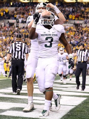 LJ Scott and Connor Cook of the Michigan State Spartans celebrate after scoring a touchdown against the Iowa Hawkeyes in the Big Ten Championship.