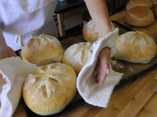Michaela Newth brings out warm bread fresh out of the ovens at Aggie Mae's in Grand Ledge on Thursday.