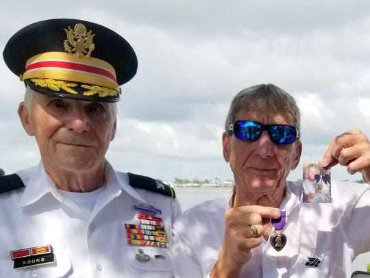Charles A. Vigilante, right, holds up a photograph