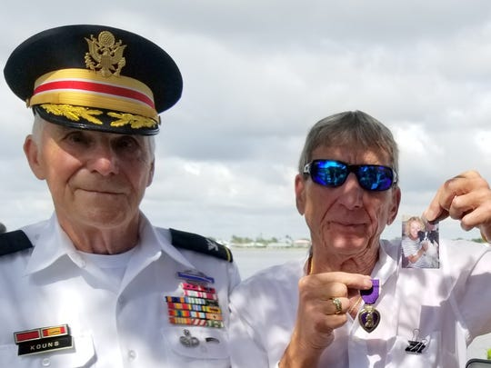 Charles A. Vigilante, right, holds upa photograph