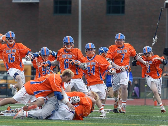 Penn Yan players storm the field following the NYSPHSAA Class C Western Semifinal on Wednesday, June 8, 2016. Penn Yan advanced to the Class C championship game with an 11-10 overtime win over Cazenovia.