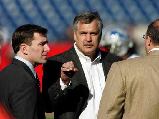Detroit Lions Matt Millen, center and Tom Lewand, left Lions Sr. VP of Finanace, talk with New England Patriots V.P. for Player Personnel Scott Pioli, right, on the field before their game in Foxboro, Mass., Sunday, Dec.3, 2006.