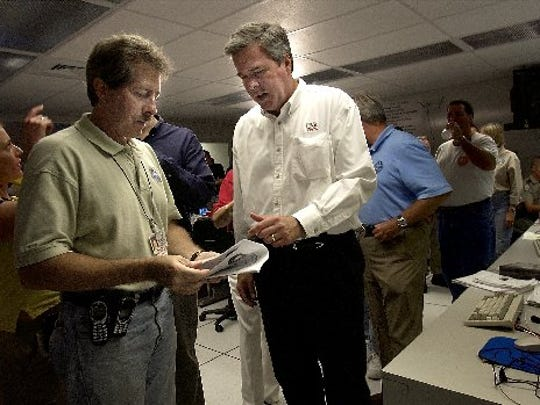 Florida Gov. Jeb Bush spoke with Martin County Administrator Russ Blackburn after a news conference concerning Hurricane Jeanne at the Martin Co. Emergency Operations Center.