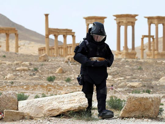 FILE -- In this April 8, 2016 file photo provided by Russian Defense Ministry press service, a Russian deminer checks for mines in the Palmyra ancient ruins, Syria. Palmyra, the archaeological gem that Islamic State fighters retook Sunday, Dec. 11, 2016, from Syrian troops, is a desert oasis surrounded by palm trees, and a UNESCO world heritage site, that boasts 2,000-year-old towering Roman-era colonnades and priceless artifacts. It is also a strategic crossroads linking the Syrian capital, Damascus, with the country's east and neighboring Iraq.