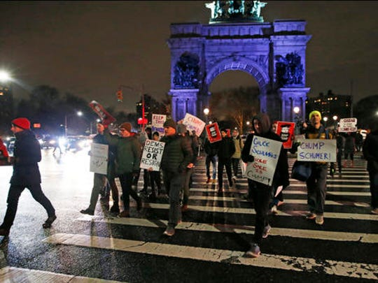 In this Tuesday, Jan. 31, 2017 photo, demonstrators protesting Senate Minority leader Chuck Schumer hold signs and chant as they march across the traffic circle at Brooklyn's Grand Army Plaza during a protest in New York. Liberals are vowing to put pressure on Schumer to mount a vigorous opposition to the agenda of President Donald Trump.