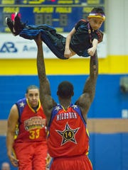 "Harlem Wizard Antoine Miguel Millien Jr. holds up Ryan Nyland, 8, from Nutley, while playing out a ""bit' with Wizard David Paul."