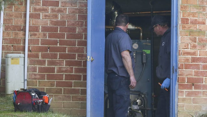 Technicians work in the utility room of an apartment building where 4 people died on March 25 in a suspected carbon monoxide leak at Riverfront Heights apartments.