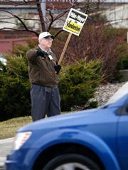 Mayoral incumbent Michael Vandersteen waves to passing motorists at 14th and Erie on a rainy election day Tuesday April 4, 2017 in Sheboygan, Wis.