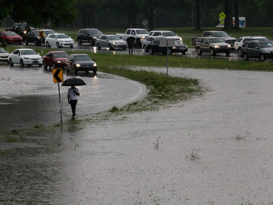 A stranded motorist walks past cars on a flooded section