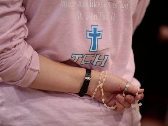 A student holds a rosary during a prayer at a  pro-life