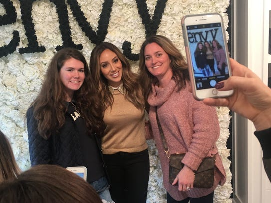 Melissa Gorga posing with fans at the reopening of
