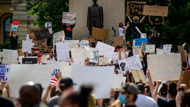 Protestors raise their signs in unison as they cheer on a speaker during a Black Lives Matter protest at the Illinois State Capitol, Monday, June 1, 2020, in Springfield, Ill.