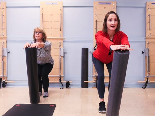 Phyllis Green, left, follows instructor Claire Greenlee's lead during a Buff Bones Pilates class at Pilates Village in St. Matthews. The class combines Pilates along with light weights to help strengthen core muscles as well as build stronger bones.