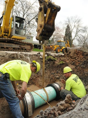Brian Hansen and Ted Dorsey splice in a section of pipe that was damaged.