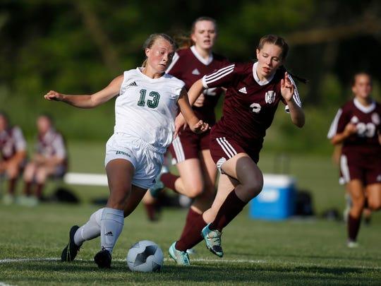 Iowa City West senior Emma Cooper (13) drives the ball