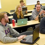 All first-year physical therapy students, Ryan Hagen and Savannah Heltzel look at something on Heltzel's laptop while Sean Connelly looks at something on his tablet behind them. Parker Reynolds converses with a fellow student who sits in front of him. They wait for the start of a class at Mary Baldwin College's Murphy Deming College of Health Sciences in Fishersville on Wednesday, Jan. 6, 2016.