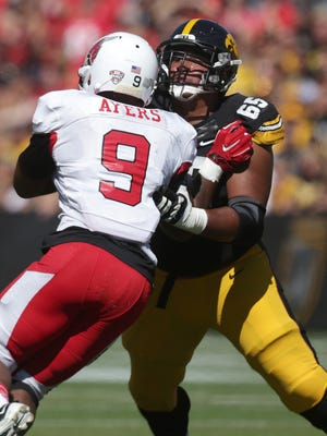 Iowa guard Jordan Walsh pushes Ball State's Michael Ayers out of the pocket on Saturday, Sept. 6, 2014, at Kinnick Stadium.