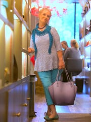 Anne Eidschun wears turquoise ankle-length cotton pants and a powder blue/periwinkle top with a turquoise lace scarf from Chico's.
