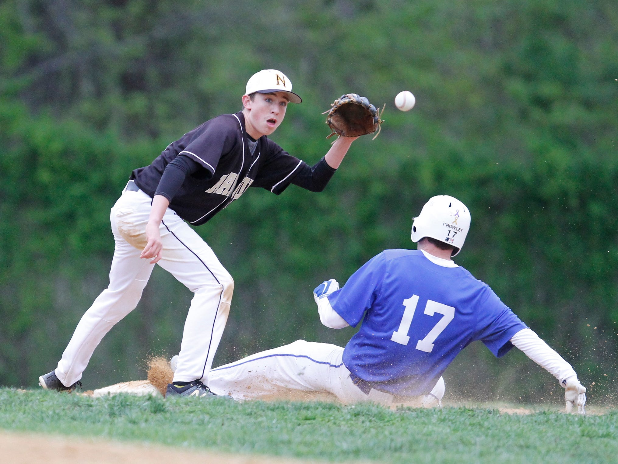 Nanuet shortstop Aiden Gallagher (10) pulls in a late throw as Hendrick Hudson base runner Mike Crowley (17) slides in safe at second during a baseball game at Sunset Park in Montrose on Thursday, May 05, 2016. Hendrick Hudson won 6-2.
