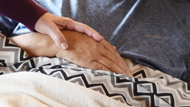 Cindy Rasmussen squeezes her husband's hand as he lies in bed in October 2015, at their Salem, Ore. home.  Dr. Peter Rasmussen, a retired oncologist and advocate for physician aid-in-dying, died in November 2015.
