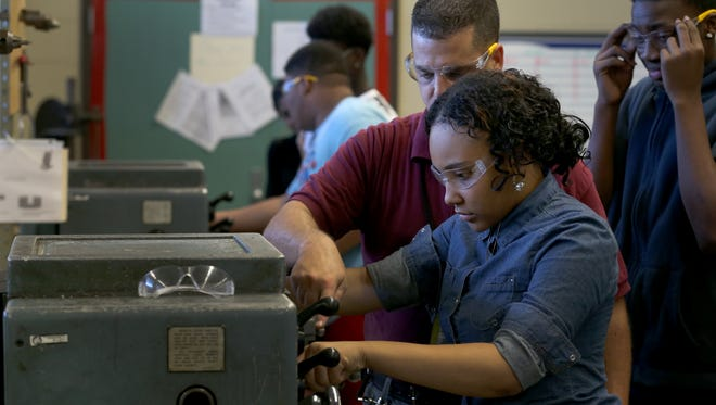 Emani Coward gets  some help from manufacturing teacher, Daniel Collins, as she fires up a lathe at Edison Tech for the first time.