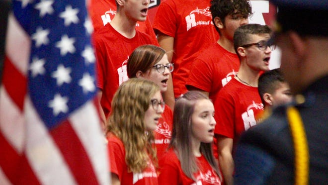 The Holland High School Choirs sing the national anthem during the school's annual Veterans Day assembly in 2019.