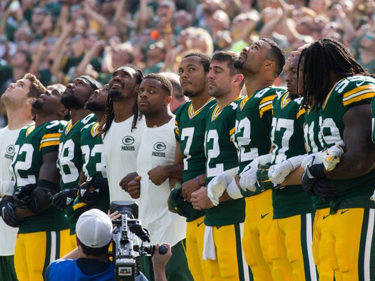 Members of the Green Bay Packers interlock their arms during the singing of the national anthem before their game against the Cincinnati Bengals Sunday, Sept.  24, 2017 at Lambeau Field in Green Bay, Wis.