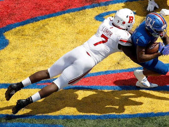 Kansas running back Pooka Williams Jr. (1) is tackled by Rutgers defensive lineman Elorm Lumor (7) during the second half of an NCAA college football game Saturday, Sept. 15, 2018, in Lawrence, Kan. Kansas won 55-14. (AP Photo/Charlie Riedel)