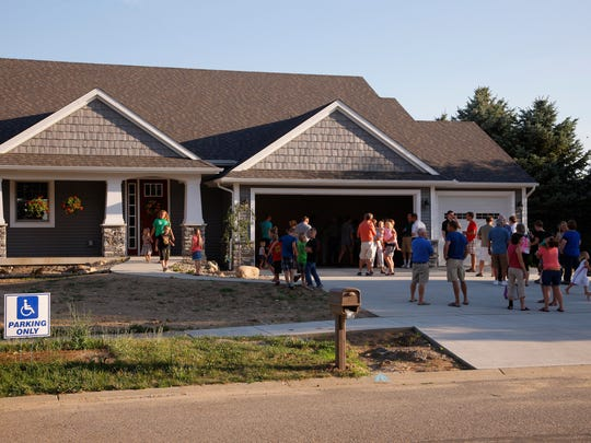 Guests gather outside at an open house for Lane and Emily Bargeron, Thursday, July 20, 2017, in St. Johns.