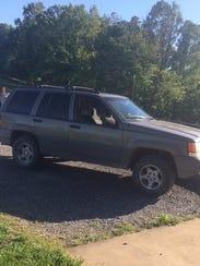 The stolen dark green 1997 Jeep Cherokee. Its license