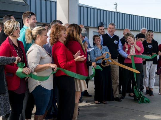 People cheer after Betsy Tillotson cuts the ceremonial ribbon for the new City of Henderson Municipal Service Center building in Henderson, Ky., Wednesday, Oct. 18, 2017.