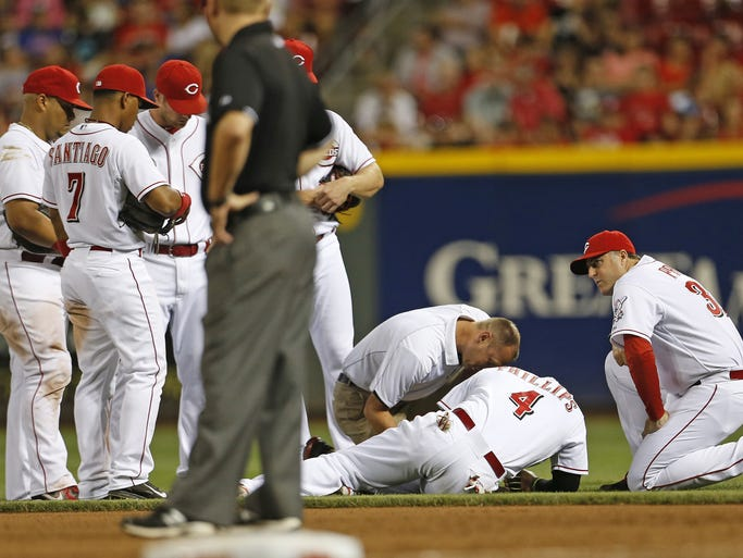 Cincinnati Reds second baseman Brandon Phillips (4)  is attended to after injuring his left thumb while diving for a ground ball.