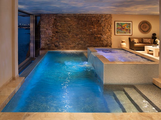 This interior pool and spa combination by B&B Pool and Spa Center features a vanishing edge over a waterfront view.