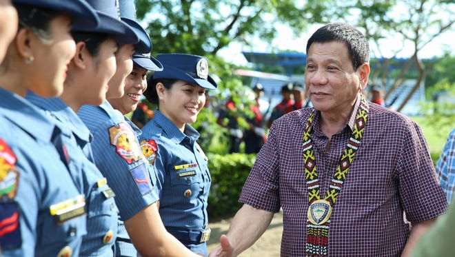 Filipino President Rodrigo Duterte shakes hands with lady police officers during a visit at a military camp in General Santos city, Philippines, on Sept. 23,  2016.