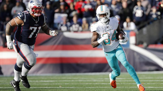 Dolphins receiver Isaiah Ford runs past New England defensive tackle Danny Shelton as part of a seven-reception performance.