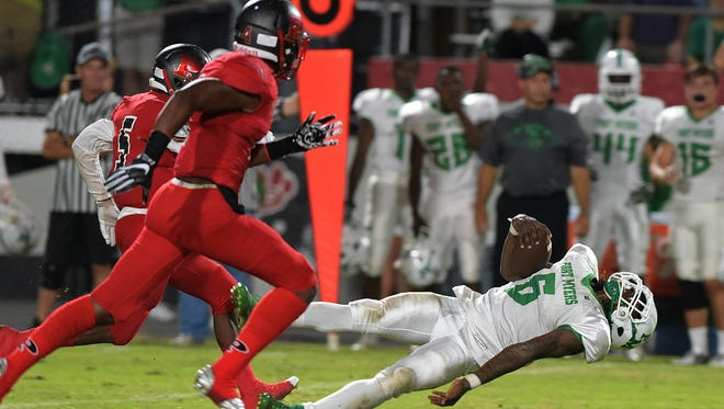Fort Myers' Darrian Felix gets airborne during Friday night's rain-delayed game against Fort Myers at Palmetto.