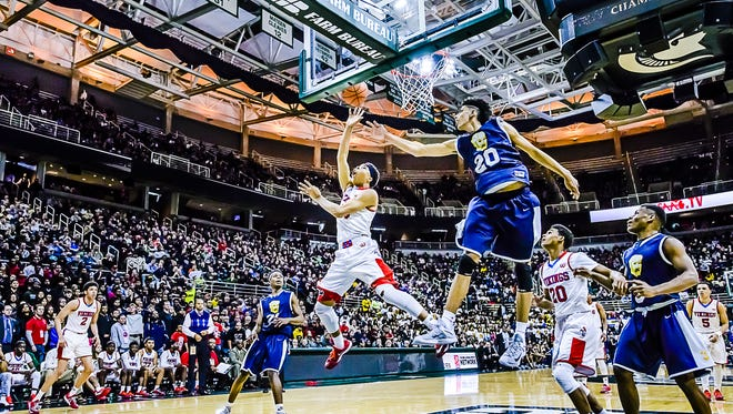 Everett's Deshae Doll lays the ball in past Saginaw Arthur Hill's Brian Bowen during a Class A state semifinal game in 2015 at Breslin Center.