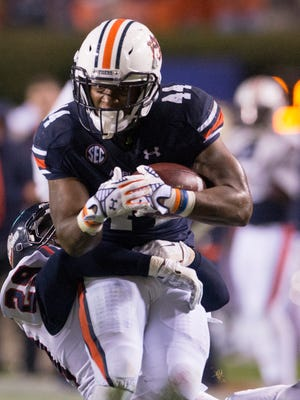 Auburn running back Cameron Artis-Payne (44) is tackled by Samford linebacker Tonne Osaigbovo (29) during the NCAA football game on Saturday, Nov. 22, 2014, at Jordan-Hare Stadium in Auburn, Ala.