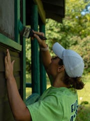 Laura Motter, trainer at FoodScience Corporation in Williston, takes on a painting project at Camp Hochelaga in South Hero.