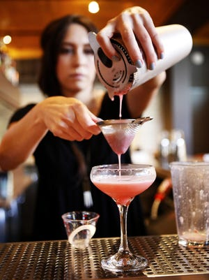 Jamie Vishnauski makes a Baya Sour with tequila, lime juice, raspberries, agave nectar, egg white and rhubarb bitters at Low Spark on Friday.