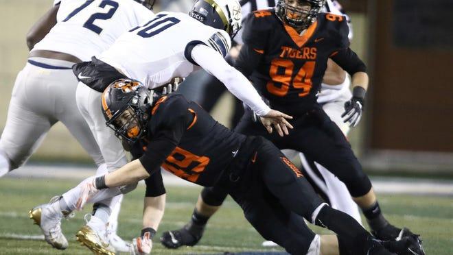 Massillon's Caiden Woullard sacks Hoban quarterback Shane Hamm in the first half. of the Tigers' regional-final win.