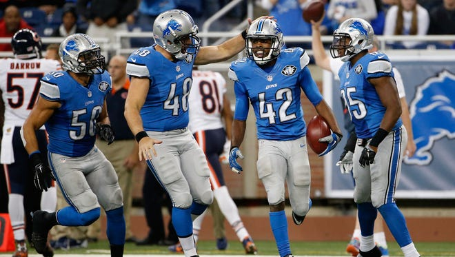 Safety Isa Abdul-Quddus #42 of the Detroit Lions is congratulated by long snapper Don Muhlbach #48 after getting a first down on a direct snap during the fourth quarter of the NFL game against the Chicago Bears at Ford Field on October 18, 2015 in Detroit, Michigan.  The Lions defeated the Bears 37-34 in overtime.