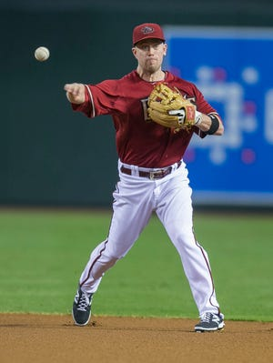 The Diamondbacks' Aaron Hill throws out a runner at first against the Rockies at Chase Field on Aug. 9, 2014.