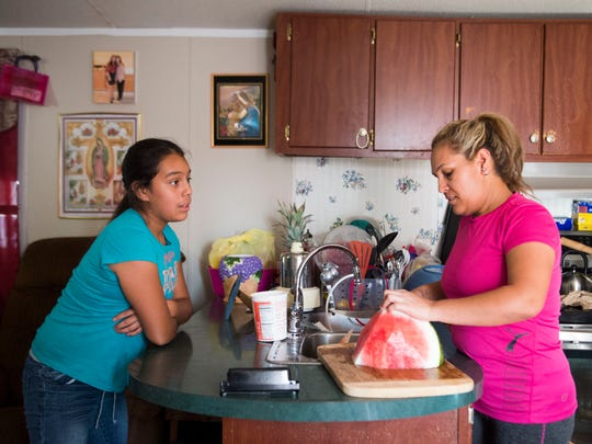 Sheryln Librado, 11, speaks with her mother Aneth as she cuts watermelon in their White Pine, Tenn. home July 3, 2018.  Aneth's husband Alberto was detained by U.S. Immigration and Customs Enforcement agents when they raided the Southeastern Provision meat-packing plant where he worked outside Bean Station in April.