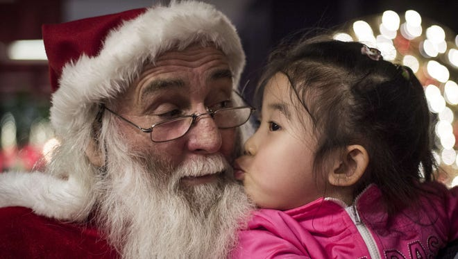 A girl kisses a Santa Claus at the Intercontinental hotel of Beijing, on Dec.19, 2014.