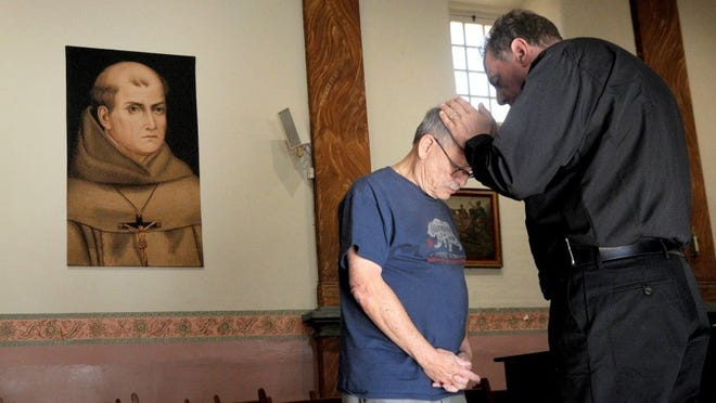 JUAN CARLO/THE STAR John Eggler, head docent at the mission, asked for a blessing by Father Albert Vanderwoerd after a Saint Junipero Serra tapestry was hung at Mission San Buenaventura on Thursday.